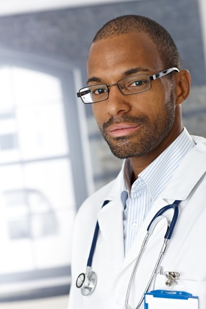 eye care professional: Closeup portrait of handsome afro medical doctor wearing smock, looking at camera.