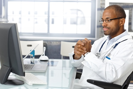 consultant physicians: Troubled doctor sitting at desk, worried, thinking hard. Stock Photo