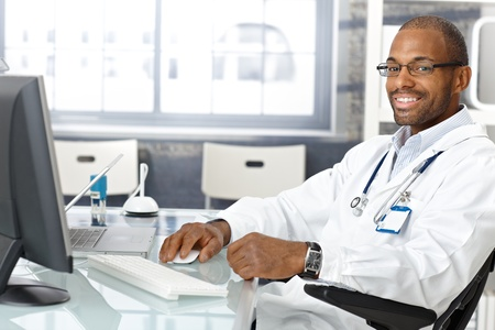 Cheerful black general practitioner working with computer in office, smiling.