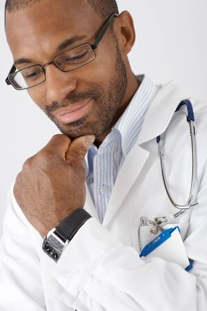 heal care: Closeup portrait of smiling ethnic doctor thinking cutout on white. Stock Photo