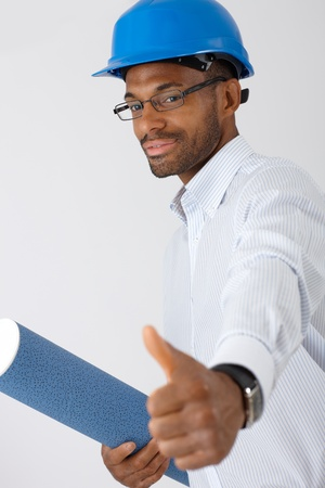 Confident afro engineer man in hardhat holding blueprint, giving thumb up. photo