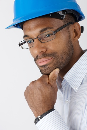 Closeup portrait of ethnic engineer in hardhat thinking. photo