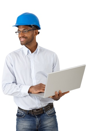 Smiling architect in hardhat working with laptop computer, cutout on white. photo