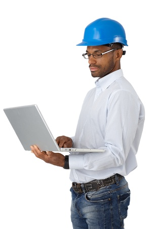 Engineer in hardhat standing, concentrating on work with laptop computer. photo