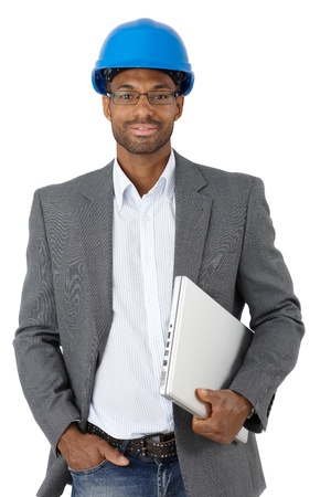 Portrait of elegant ethnic engineer in hardhat with laptop computer, smiling at camera. photo