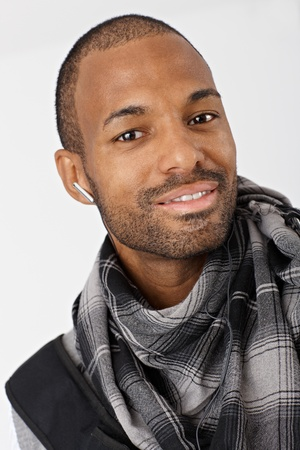 Closeup portrait of ethnic guy smiling wearing scarf and earbuds. photo