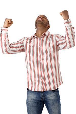 Happy ethnic guy celebrating good news, winning, success, fist and arms raised, smiling. Stock Photo - 12471703