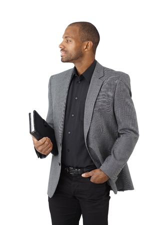 Portrait of elegant ethnic businessman with personal organizer, side view, cutout on white. photo