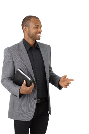 Smiling Afro-American businessman with personal organizer pointing, cutout on white. photo