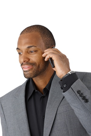 Smiling black businessman in smart suit on mobile phone call, cutout on white. photo