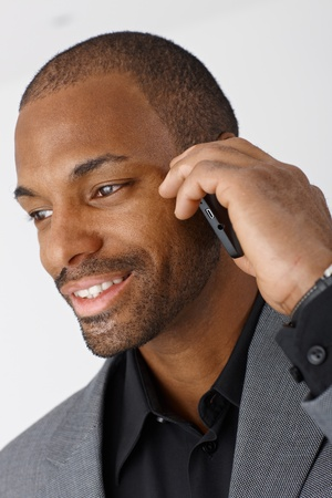 Closeup portrait of Afro-American businessman talking on mobile phone, smiling. photo