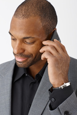 Smiling ethnic businessman concentrating on mobile phone call, closeup portrait. photo