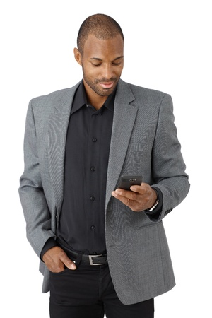afro man: Handsome elegant ethnic businessman texting on mobile phone, smiling, cutout on white.