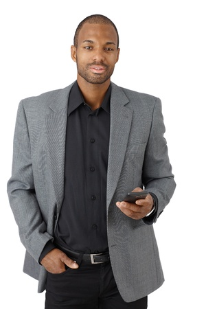Portrait of confident elegant businessman with cellphone handheld, texting, looking at camera, isolated on white. photo