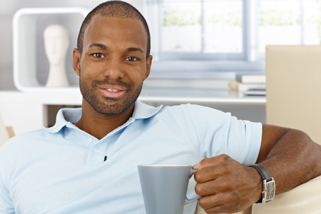 in black: Portrait of cheerful handsome black man sitting at home with mug handheld, drinking tea, smiling at camera. Stock Photo