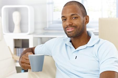 Happy man having tea at home, sitting in living room, mug handheld, smiling at camera, casual leisure. photo