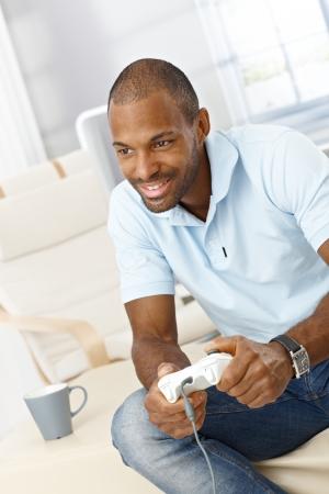 jugando videojuegos: Sonriente hombre que juega con la consola de juego de ordenador joystick, sentado en la sala.