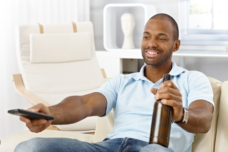 Smiling afro man enjoying leisure time in living room, with beer and remote control. photo