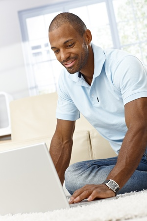 Smiling black man using laptop computer at home, sitting on floor. photo