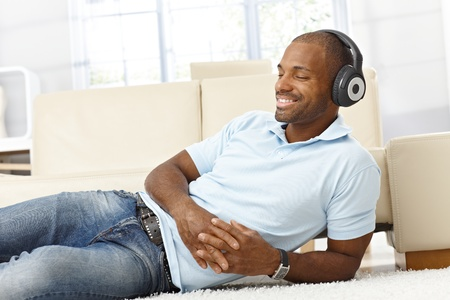 Handsome black man enjoying listening to music on headphones, lying on living room floor, smiling with eyes closed.