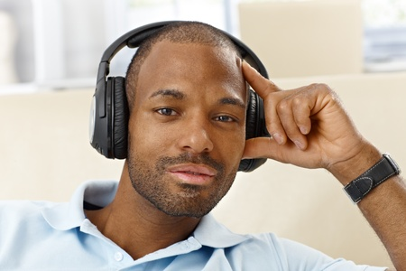 Portrait of handsome ethnic man with headphones, looking at camera, thinking. photo