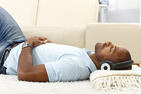 Portrait of casual guy relaxing with music on headphones at home, lying on floor.