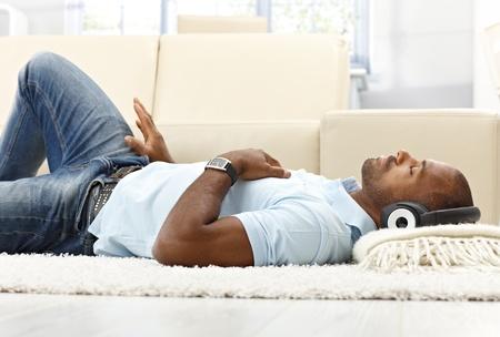 closed eyes: Vrije tijd met muziek, etnische man liggend op vloer van de woonkamer met headset, genieten met gesloten ogen.