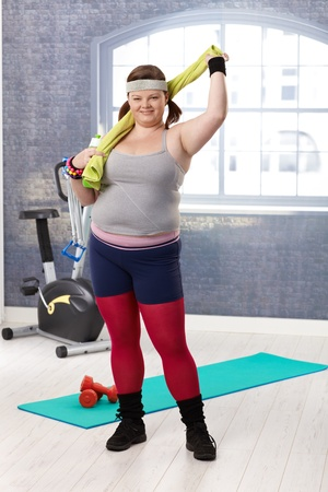 Plump woman at the gym in sportswear, smiling. Stock Photo