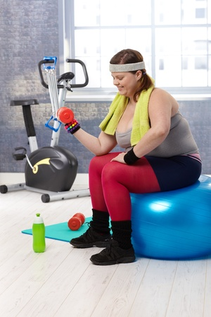 Plump woman exercising with dumbbells at the gym. photo