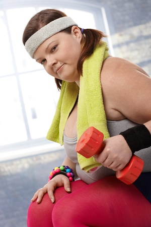 stockphoto: Determined fat woman exercising with dumbbells.