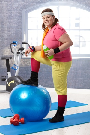 overweight women: Young fat woman taking a break at the gym, resting leg on fit ball, drinking water.