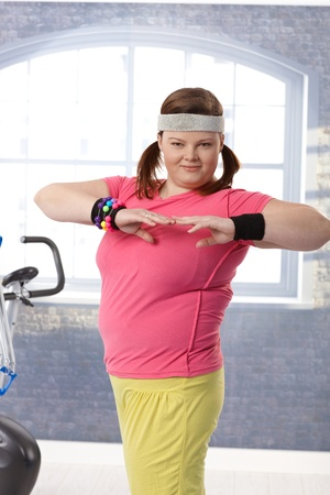 Happy plump woman exercising in colorful outfit at the gym. Stock Photo - 12472234