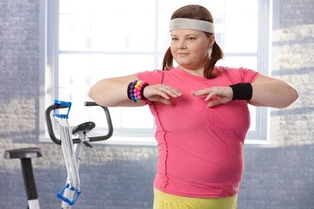 Overweight young woman exercising at the gym. photo