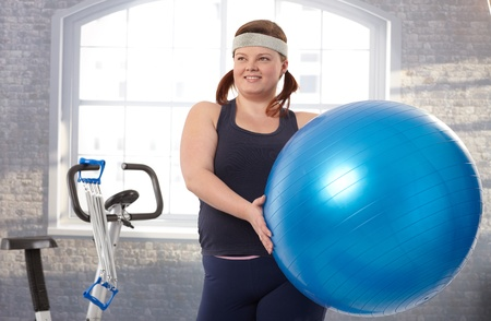 Young fat woman exercising with fit ball at the gym. Stock Photo - 12472226