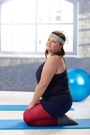 kneeling woman: Overweight woman doing gymnastics at the gym.