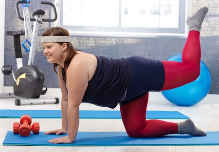 sport wear: Young fat woman doing gymnastics at the gym, smiling.
