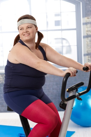 Fat woman smiling on exercise bike at the gym. photo