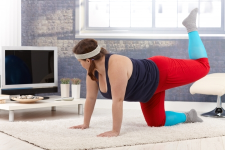 Plump woman exercising at home on floor. photo