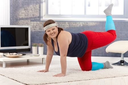 Happy young fat woman exercising at home on floor, smiling. photo