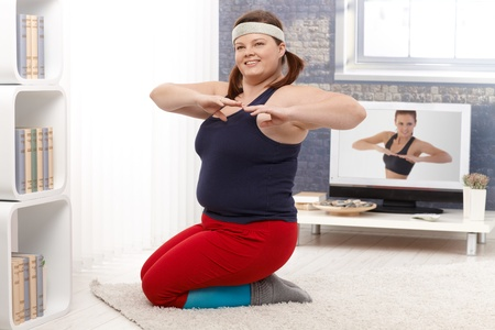 Young plump female doing workout at home, smiling. Stock Photo - 12472231