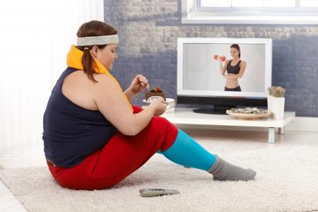 sobre peso: Mujer gorda sentada en el suelo con el pastel de chocolate mientras ve el programa de fitness en la televisión. Foto de archivo