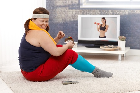 Overweight woman sitting on floor watching fitness program on television and eating chocolate cake, smiling. photo