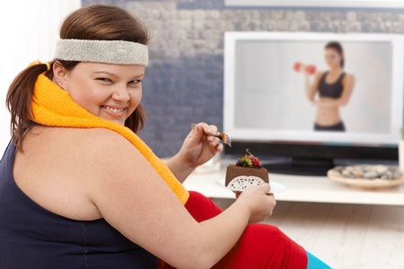 Fat woman choosing chocolate cake instead of doing gymnastics, smiling happily. photo
