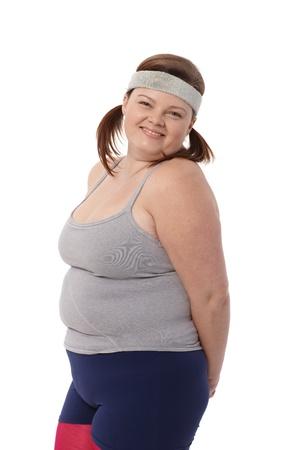 donne obese: Ritratto di donna felice in sovrappeso sportswear su sfondo bianco.