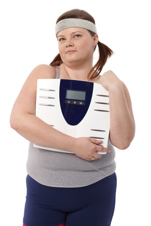Fat woman in sportswear holding a scale in hands, daydreaming. photo