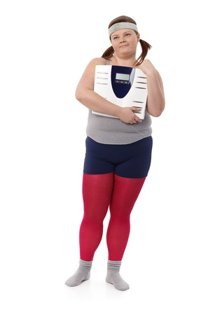Plump woman in sportswear holding a scale in hands, looking away. photo