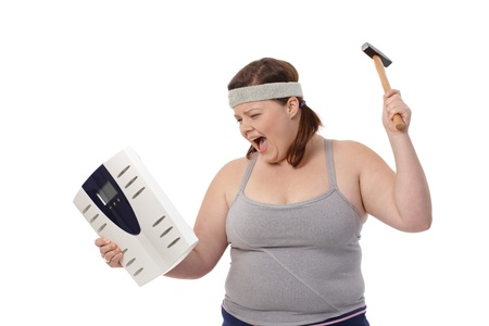scale weight: Angry fat woman punching scale by hammer, shouting.