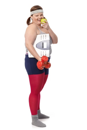 Fat woman dieting with scale, green apple and dumbbells. photo