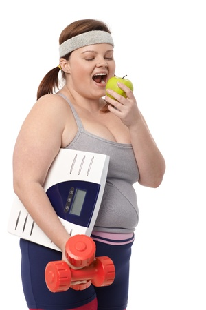 Plump woman biting green apple, holding dumbbells and scale in sportswear. photo