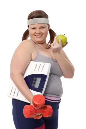 Happy fat woman eating green apple, holding dumbbells and scale in sportswear. photo